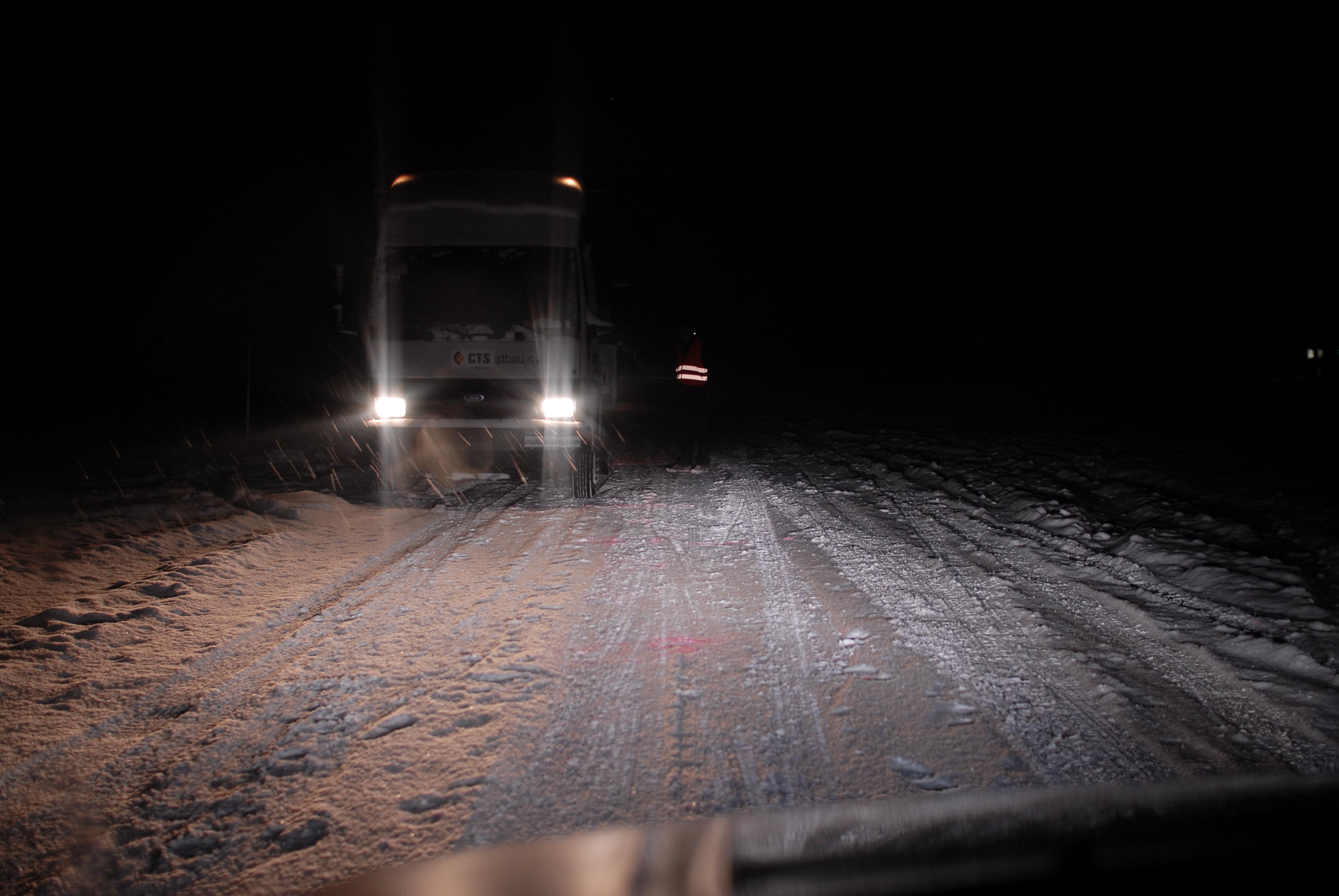Sicht auf einen neben dem Lkw stehenden Fußgänger bei Schneetreiben